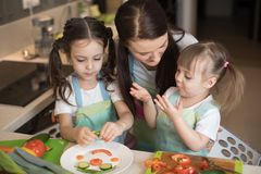 Happy family mother and her kids are preparing healthy food, they improvise together in the kitchen royalty free stock photo