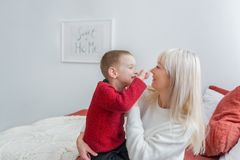 Happy family mother and her son, hugging and laughing in bed royalty free stock image