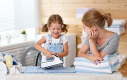 Happy family mother housewife and child daughter ironing clothes Royalty Free Stock Photography