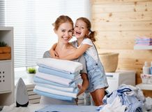 Happy family mother housewife and child daughter ironing clothes Stock Photography