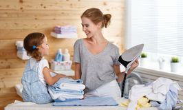 Happy family mother housewife and child daughter ironing clothes Royalty Free Stock Images