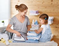 Happy family mother housewife and child daughter ironing clothes Stock Image