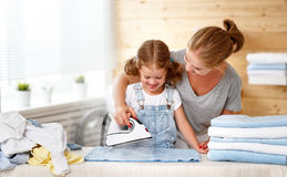 Happy family mother housewife and child daughter ironing clothes Royalty Free Stock Photos