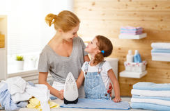 Happy family mother housewife and child daughter ironing clothes Royalty Free Stock Image