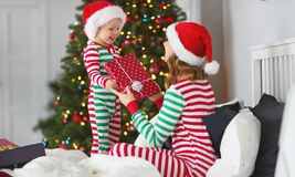 Happy family mother hug her baby son in pajamas opening gifts o royalty free stock photos