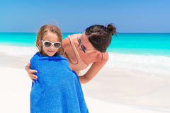Happy family of mother and kid on the beach vacation. Little girl in towel on the seashore Stock Photography