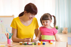 Happy family mother and kid daughter paint together. Adult woman helps child girl. Royalty Free Stock Image