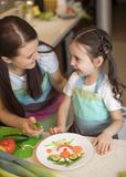 Happy family mother and kid girl are preparing healthy food, they improvise together in the kitchen royalty free stock photo