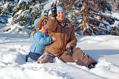 Happy family of mother with kid playing in the winter park Stock Image