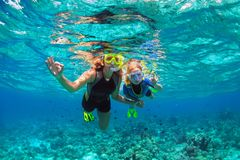 Mother, kid in snorkeling mask dive underwater with tropical fishes royalty free stock photography