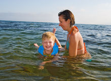 Happy family of mother with kid in the waves on the sea Royalty Free Stock Photos