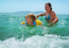 Happy family of mother with kid in the waves stock images