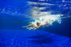 Kids with mother dive in swimming pool stock images