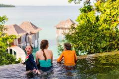 Mother and kids at swimming pool. Happy family mother and kids at outdoors infinity swimming pool enjoying views Stock Photography