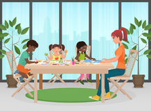 Happy family. Mother and kids together paint. Adult woman helps and teach childrens how to drawing. Royalty Free Stock Photography