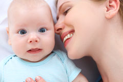 Happy family mother kisses and hugs her baby Royalty Free Stock Photography