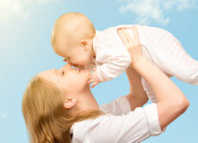 Happy family. Mother kissing baby in the sky Royalty Free Stock Photos
