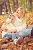 Happy family mother and little daughter play cuddling in autumn park. Stock Image