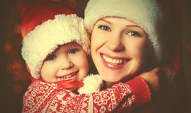 Happy family mother and little daughter playing in Christmas. Happy family mother and baby little daughter playing in the winter for the Christmas holidays stock photo