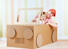Happy family mother and little daughter ride on toy car made of cardboard. On vacation royalty free stock photo