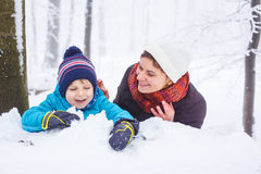 Happy family: mother and little son having fun with snow in wint Stock Photography