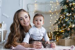 Mom with a small son near a beautiful Christmas tree in his house Stock Images