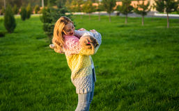 Happy family. Mother playing with her daughter on green lawn with grass Stock Photo