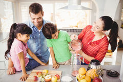 Happy family with mother pouring fruit juice in jug Royalty Free Stock Photography