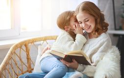 Happy family mother reads book to child to daughter by window royalty free stock photo