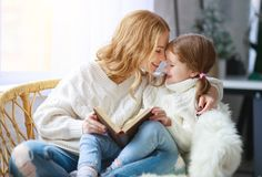 Happy family mother reads book to child to daughter by window stock images