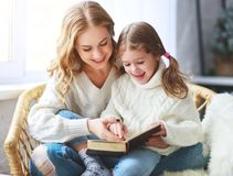 Happy family mother reads book to child to daughter by window royalty free stock photography