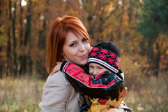 Happy family, mother and son in autumn forest Royalty Free Stock Images
