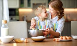 Happy family mother and son bake kneading dough in kitchen royalty free stock image