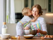 Happy family mother and son bake kneading dough in kitchen stock photos