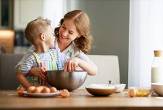 Happy family mother and son bake kneading dough in kitchen royalty free stock photos
