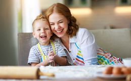 Happy family mother and son bake kneading dough in kitchen. Happy family mother and child son bake kneading dough in the kitchen royalty free stock photo