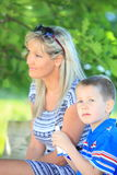 Happy family mother and son on bench in park Royalty Free Stock Images