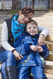 Happy family mother and son on bench. Royalty Free Stock Image