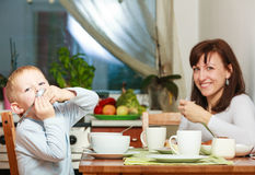 Happy family. Mother and son boy kid child eating breakfast together Stock Image