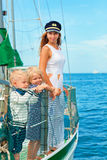Happy family - mother, son, daughter on board of sailing yacht. Happy family - mother in captain cap, baby son, daughter on board of sailing yacht. Children Stock Photography