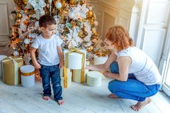 Mother and son near Christmas tree at home stock images