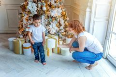 Mother and son near Christmas tree at home stock photo