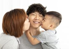 Family mother and son kissing father. Happy family mother and son kissing father royalty free stock photo