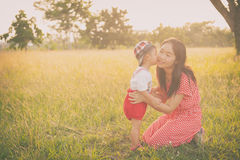 Happy family. A mother and son kissing in grass fields outdoors Stock Photography