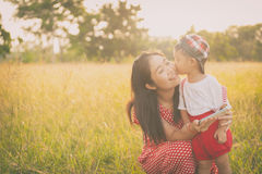 Happy family. A mother and son kissing in grass fields outdoors Royalty Free Stock Photo