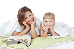 Happy family - mother and son lying on the white bed Stock Images