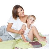 Happy family - mother and son lying on the white bed Stock Image