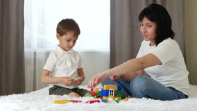 Happy family: mother and son play building a house of coloured blocks. The child and mother play and laugh.