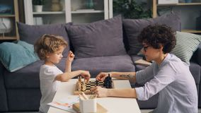 Happy family mother and son playing chess at home moving pieces on board