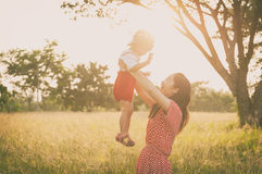 Happy family. A mother and son playing in grass fields outdoors Stock Image
